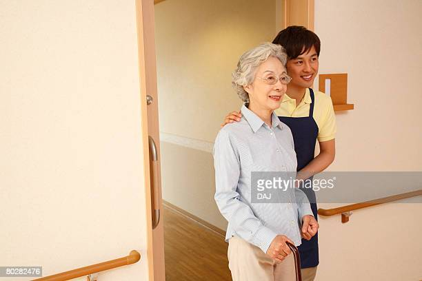 A Young Care Worker and A Senior Adult Woman Standing at the Door