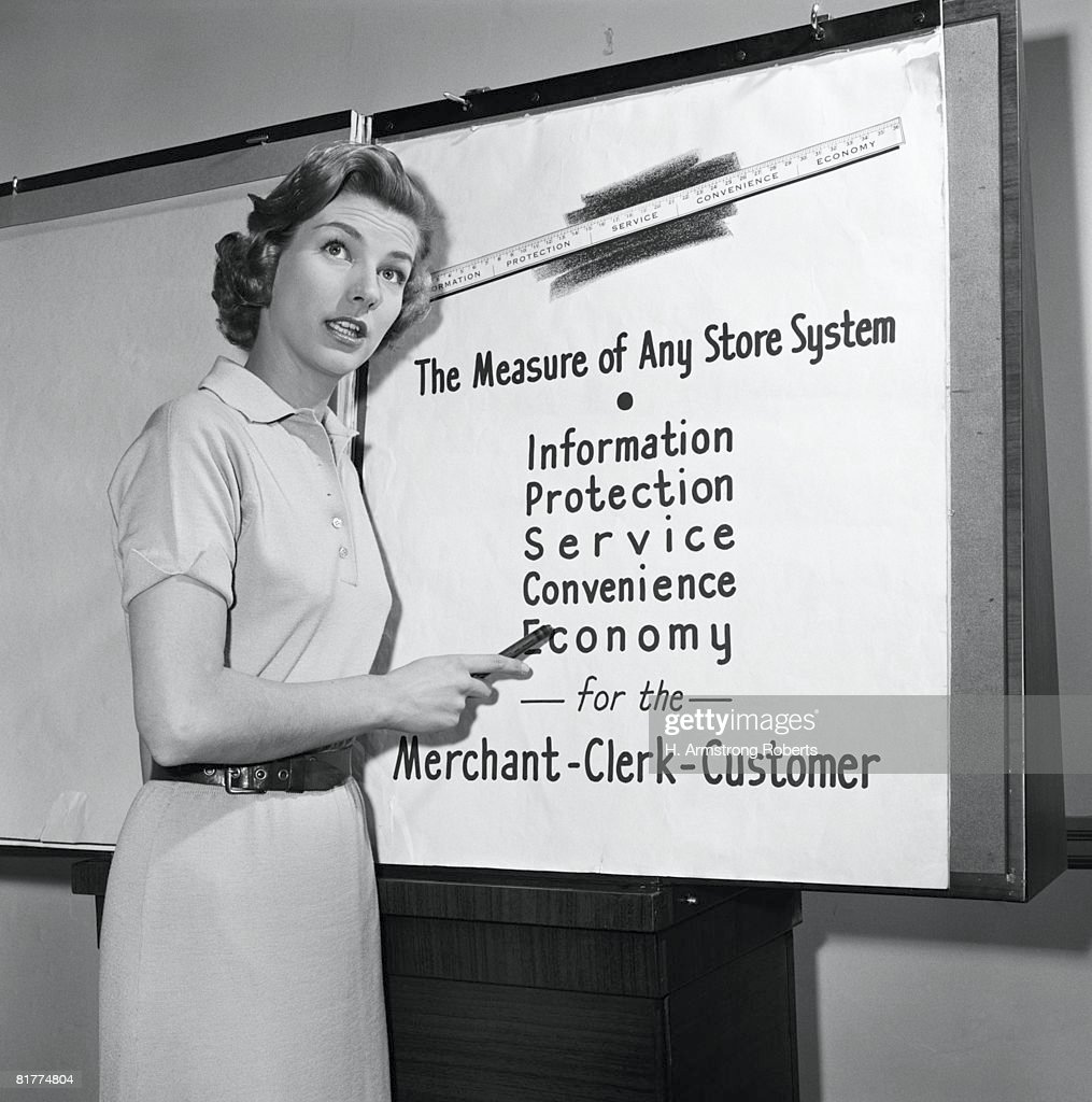 Young career woman giving business presentation, pointing at poster. : Stock Photo