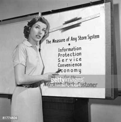 Young career woman giving business presentation, pointing at poster. : Foto de stock