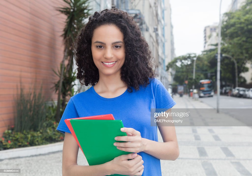 Young caribbean student with books in the city : Stock Photo