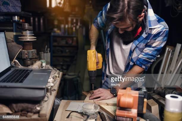 Junge Tischler Bohren eine Planke in seiner Werkstatt