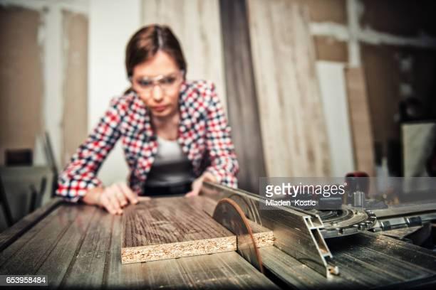 Young carpenter, repairwoman using a circular saw
