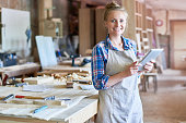 Portrait of happy young woman looking at camera using digital tablet in modern woodworking shop, copy space