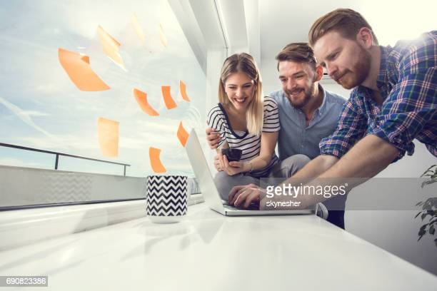 Young casual business team writing an e-mail on a coffee break.