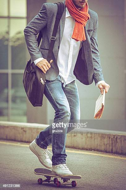 Young casual businessman commuting to work skateboarding.