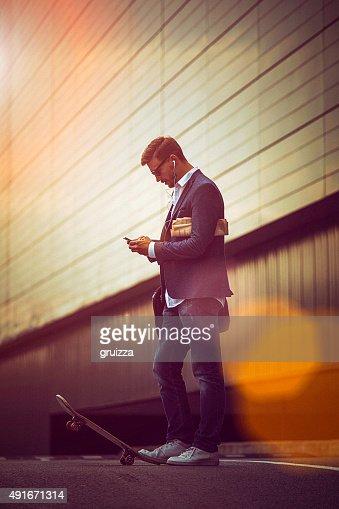 Giovane casual Uomo d'affari utilizzando uno smartphone nella urban environme
