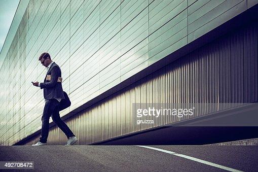 カジュアルな若いビジネスマンはスマートフォンを使用して、都会的な環境