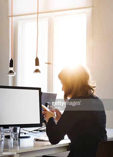 Junge Casual Geschäftsfrau mit Smartphone im Start-Up-Büro
