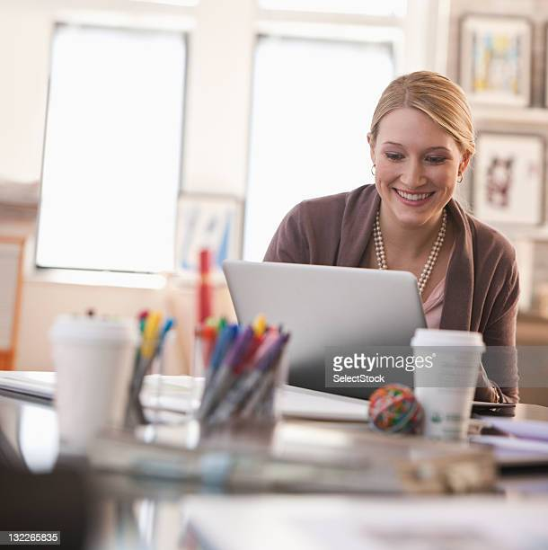 Young casual businesswoman  working on laptop