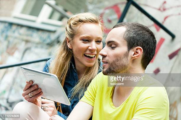 Young casual couple using digital tablet outdoors