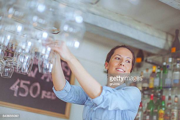 Young, casual female bartender arranging wineglasses at the bar