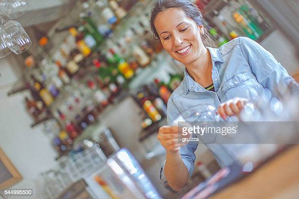 Young, casual female bartender cleaning wineglass at the bar counter