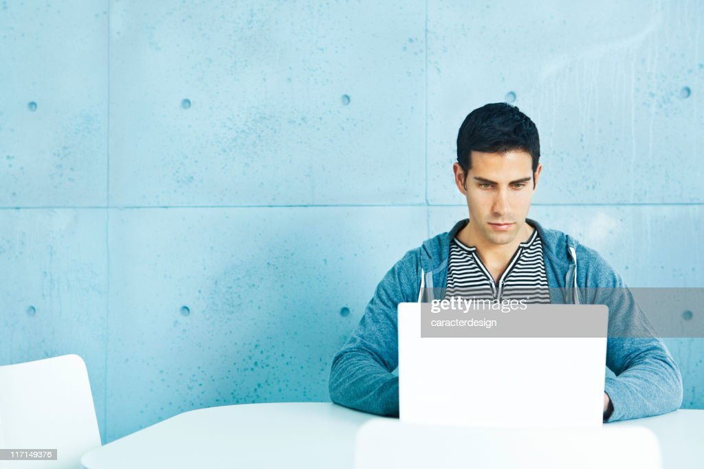 Young casual man using laptop : Stock Photo