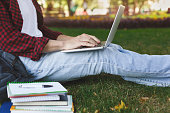 Young casual man with laptop outdoors. Male student preparing for exams with computer and books in the park. Education and entering the university concept, crop, copy space.