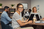 Beautiful latin businesswoman looking at camera and smiling while working in office. Cheerful young woman wearing spectacles and holding digital tablet. Creative girl working with colleagues at agency