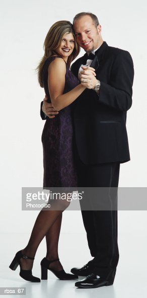 young caucasian adult blonde female wearing short purple silk sleeveless dress and heels standing in dance position with young caucasian adult balding male with facial hair wearing tuxedo looking as a couple at the camera and smiling