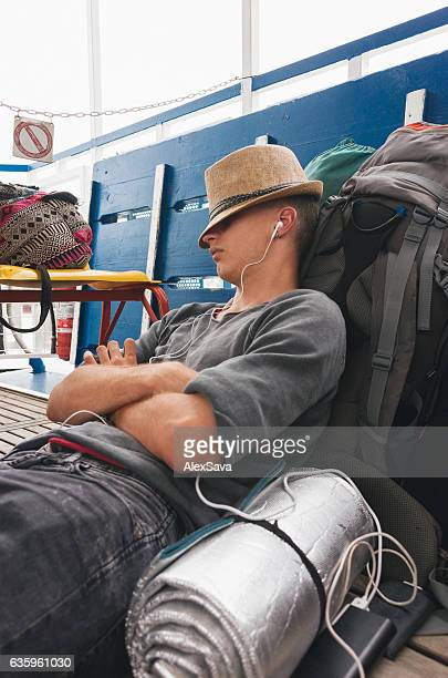 Young caucasian backpacker man taking a nap on his luggage