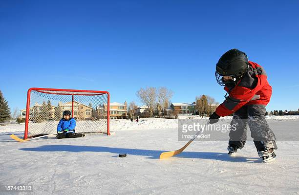 Young Caucasian Children Playing Ice Hockey on Outdoor Rink