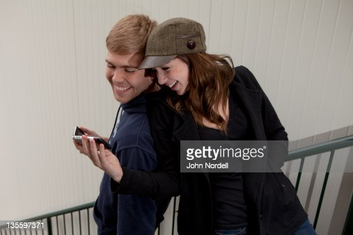 Young Caucasian couple, 20-21 years old, texting each other and friends : Stock Photo