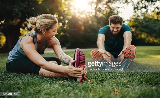 Young caucasian couple exercising in park : Stock Photo