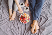Young caucasian couple having romantic breakfast in bed. Closeup of female and male feet, two cups of coffee, fruits and colorful biscuits.