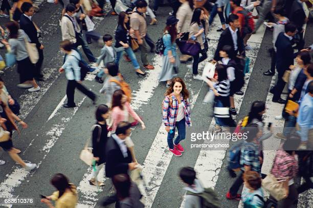 Young caucasian girl is smiling confused losted in Tokyo crowd