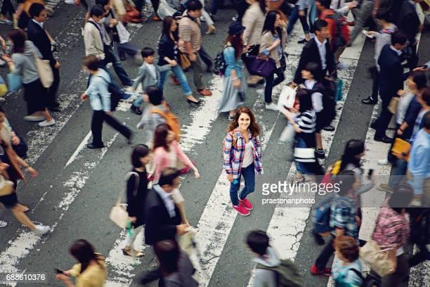 Joven caucásica está sonriendo confuso curarle en multitud de Tokio