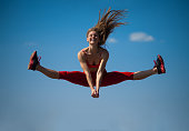 Young caucasian girl performs twine jumping on sky backround. Lifestyle and sport concept