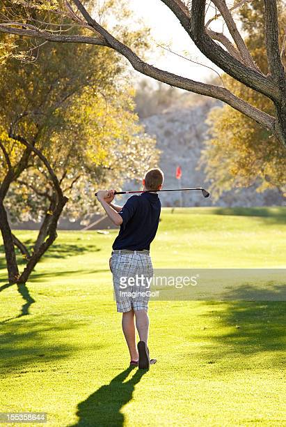 Young Caucasian Male Golfer Swinging Golf Club