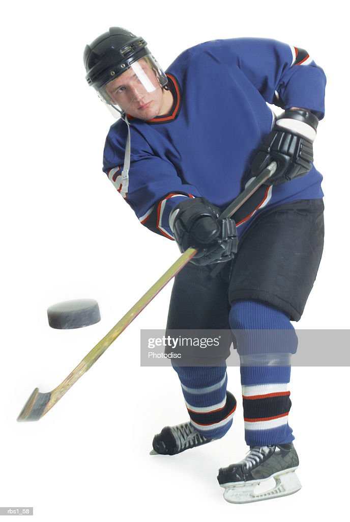 A young caucasian male hockey player in a blue uniform shoots the puck towards the camera with his hockey stick