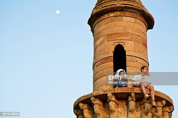 Young Caucasian man and Indian woman sitting at the top of one of the two minarets at the Kevda Masjid mosque in Champagner India