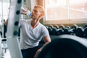 Young Caucasian man in white shirt at a gym, sitting on bench and drinking water from bottle. Thirsty and dehydration from workout and losing too much sweats. Sport fitness after training concept