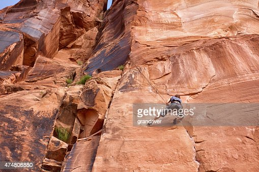 Giovane caucasico di uomo di arrampicata su una parete rocciosa vicino Moab