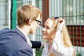 young caucasian man is pressing his girlfriend to the fence at sunny summer day