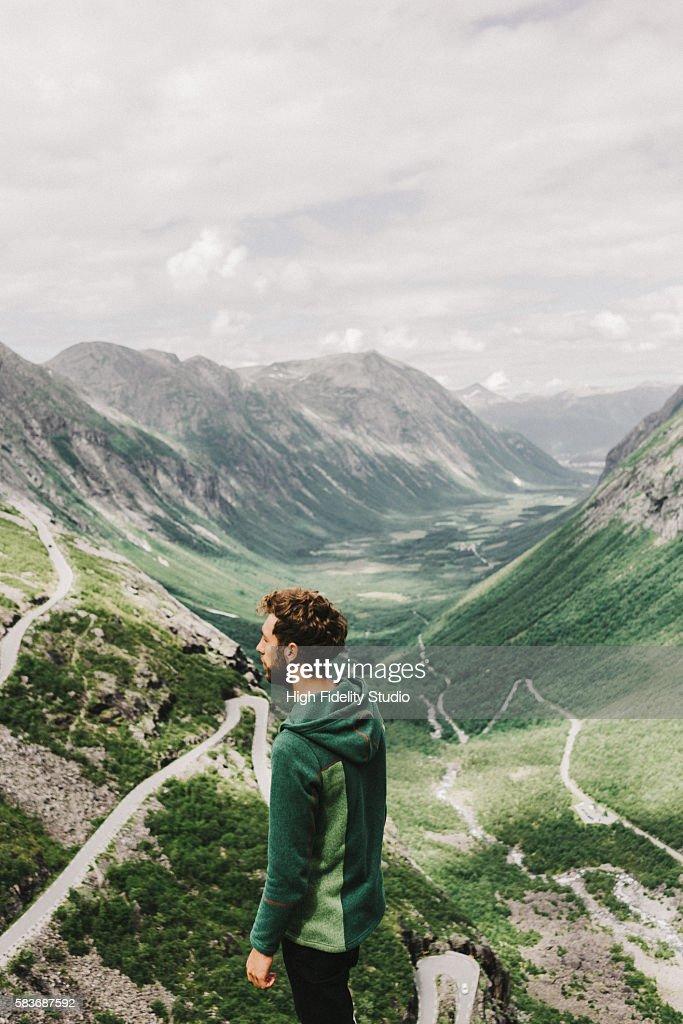 Young Caucasian man looking at Trollstiegen road