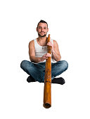 young caucasian man play music on his didgeridoo (Australian national musical instrument)