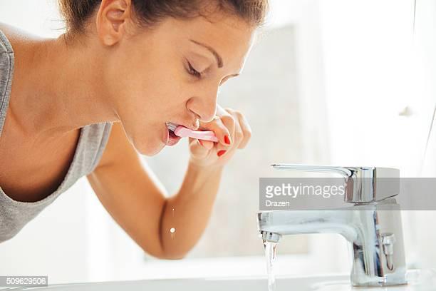 Jovem mulher caucasiana escovagem os dentes em casa de banho na manhã