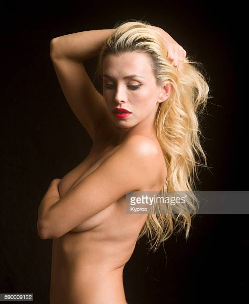 Young Caucasian Woman Covering Her Chest With Her Arms, Close Up, Studio Shot
