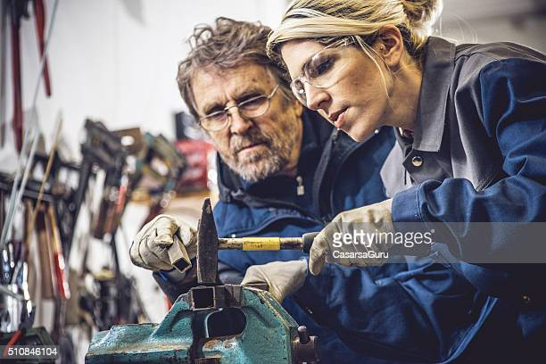 Young Caucasian Woman Using Hammer in Mechanical Workshop