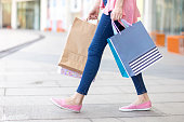 Young Caucasian woman wearing jeans holding shopping bags and walking in street