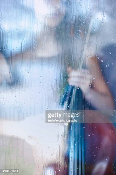 young cellist by a rainy window