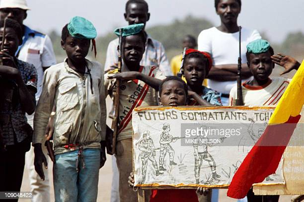 Young Chadian boy scouts parade with wooden rifles on February 23 in Doba next to a banner which revels 'future fighters of Chad' during the...