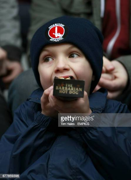 A young Charlton Athletic fan enjoys a hotdog in the stands