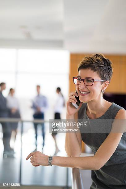 Young cheerful businesswoman using mobile phone indoors