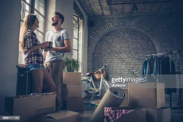 Junge fröhliche paar Kommunikation nach Ihrem Umzug in neue Wohnung.