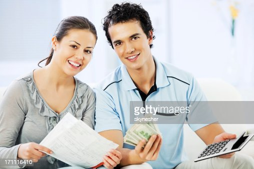 Young cheerful couple doing their taxes. : Stock Photo