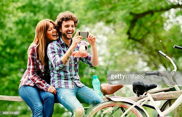 Joven Alegre pareja bebiendo agua y vista del smartphone.