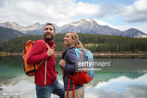 Young cheerful couple hiking by the lake in Autumn