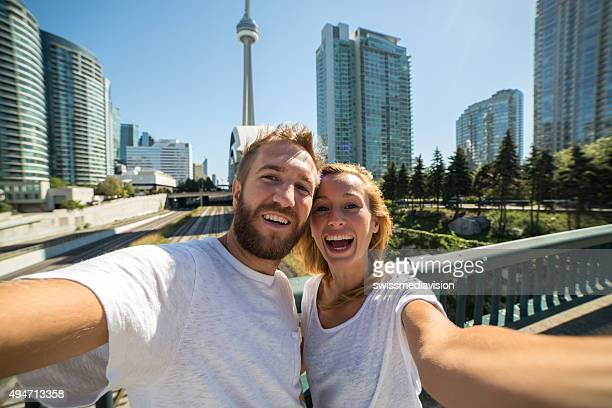 Young cheerful couple in Toronto taking selfie portrait with cityscape