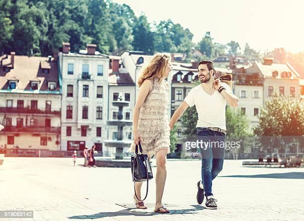 Junge fröhlich paar Einkaufsmöglichkeiten und zu Fuß von der Straße